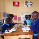 "At Judith's Reading Room Muhanga, children spread their books on the table. ""Teacher, look what I found!"" ""Look! Look!"" They are SO excited!"